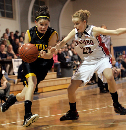 Danvers: Bishop Fenwick's Lizzy Trainor is defended in front of the net by Reading's Carlene Kluge during last night's Division 2 North playoff semifinal held at St. John's. Photo by Deborah Parker/Salem News Wednesday March 4, 2009.