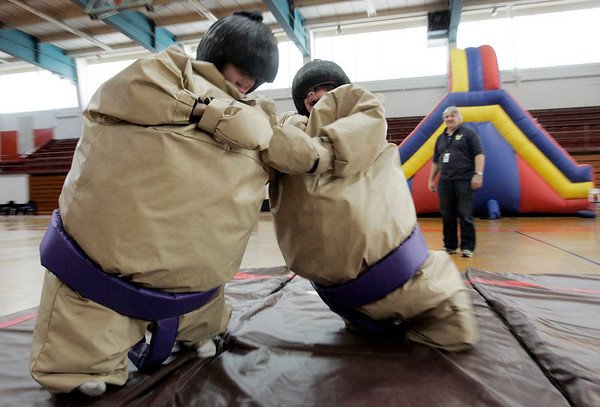 Beverly: Logan Stevens, 9, of Beverly tries with all her might to push her brother, Dylan, 11, over while sumo wrestling at All About Fun Inc.'s fundraiser for the North Shore Music Theatre held at Beverly High School Saturday. All About Fun is a party rental company located in Boxford.  They have taken direct action to help the North Shore Music Theatre with their ÒSave Our TheatreÓ Campaign. The event featured an obstacle course, a velcro wall, carnival games, food and face painting. Photo by Deborah Parker/Salem News, Saturday, January 17, 2009.