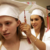 Marissa Paci of Boxford fastens the cap of Katie Mulholland of Middleton with bobby pins before the start of graduation at Masconomet Regional High School Friday evening. Photo by Deborah Parker/ June 5, 2009