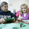 Katie Dollard, a junior at Danvers High School helps, Julia Vaillancourt, a Highlands School first grader, create a wreath from craft paper Monday afternoon. The arts and crafts program was held as part of a Commuinty Service Learning project by  Dollard. All the proceeds from the program will be dontated to Strays In Need. Photo by Deborah Parker/December 14, 2009