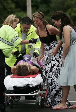 """Members of Beverly High School peer leadership team along with the Police and Fire departments simulate an after party car crash in a parking lot at the school Wednesday. In preperation for prom the mock crash was held to encourage students to realize what could happen if they drink and drive after prom or any event. Here, peer leaders Meg Finn and Courtney Chalifour talk to Erin Bushey as she is cared for by paramedics after being removed from the """"crash"""". Photo by Deborah Parker/June 10, 2009"""