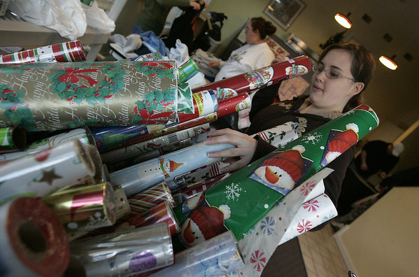Beverly : Beverly Bootstraps intern, Florencia Sobral, who is attending Endicott College, organizes as stack of wrapping paper as part of Beverly Bootstraps Adopt-a-family program. Annonymous people donated gifts to Bootstraps which they then gave out. Thursday people could come and collect the gifts and also pick up wrapping paper and bows to wrap them with.  Photo by Deborah Parker/Salem News Thursday, December 18, 2008