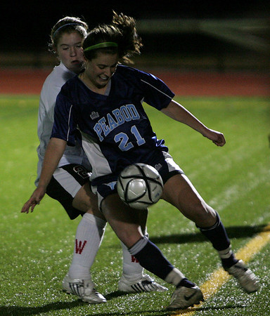 Peabody's Hayley Dowd fights to maintain control of the ball over Winchester's Katherine Zavaz in yesterday's Division 1 North Semifinals held at Woburn High School. Photo by Deborah Parker/November 12, 2009