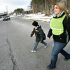 Shannon Underwood, a student at Danvers High School, helps Smith Elementary school student, Matthew Downey, cross the street at her bus stop after school. Underwood is a new monitor for the school bus and will ride the bus with students as part of a program aimed at reducing bullying. Photo by Deborah Parker/January 13, 2009