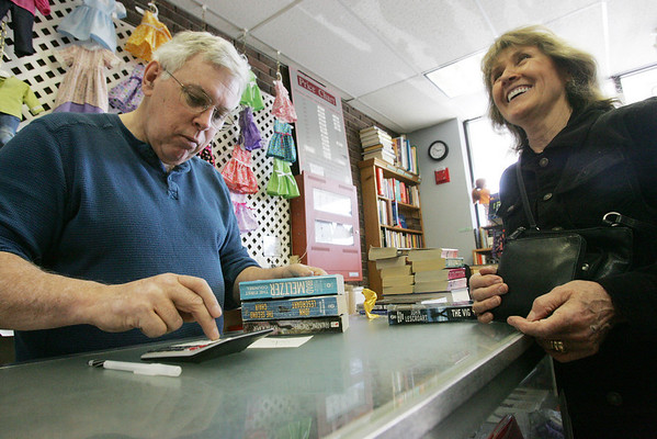 Peter Smyth of Danvers owns Hand-It-Back Booksmyth in Middleton. When he was diagnosed with cancer, people volunteered to work at his shop to keep it open. Today he's back at work. Here he rings up customer Bernice Stefl of Middleton. Photo by Deborah Parker/April 13, 2010