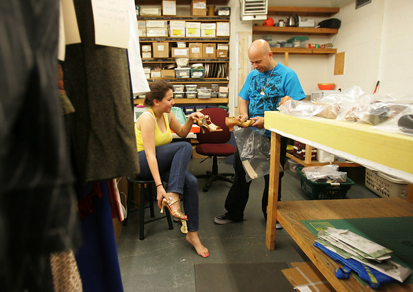 Alliy Drago, part of the women's ensemble of the new Gypsy production at the North Shore Music Theatre tries on shoes with Jose Rivera, the costume coordinator, yesterday, in preperation for the shows opening next week. The Theatre is reopening after being closed for more than a year. Photo by Deborah Parker/July 1, 2010