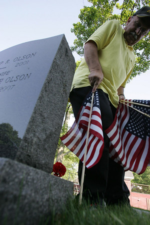 Beverly veterans agent Jerry Guilebbe places a flag at a gravestone in Central Cemetary Wednesday evening in honor of the upcoming Memorial Day holiday. A group of veterans worked to place flags around town. Photo by deborah parker/may 26, 2010