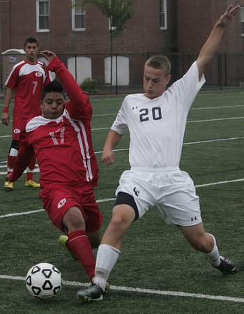 St. John's Tyler Newhall and Everett's Marvin Garcia both stretch for the ball during yesterday's game held at St. John's Prep in Danvers. Photo by Deborah Parker/September 27, 2010