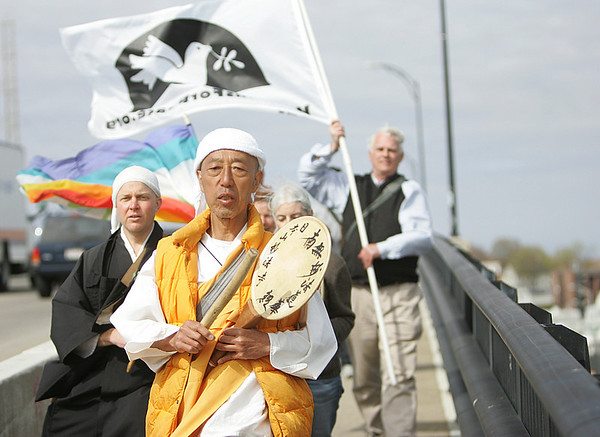 Buddhis monks and local walkers from Salem walked over the Veterans Memorial bridge as part of a walk to the U.N. Review Conference of the Nuclear Non-Proliferation Treaty. From left, is Kenzan Seidenberg of Vermont, Gyoway Kato of Massachusetts and John Schuchardt of Ipswich House of Peace. Photo by Deborah Parker/April 8, 2010