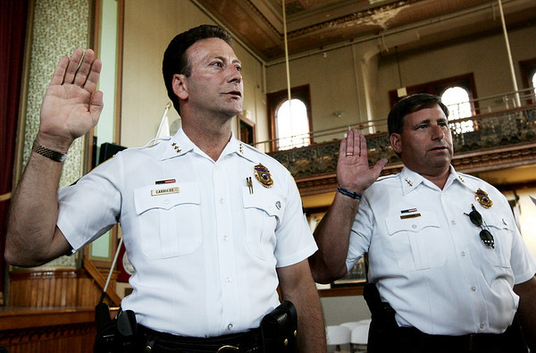 Scott Carriere and Martin Cohan are sworn in as Deputy Chiefs of the Peabody Police Department by City Clerk Tim Spanos at City Hall yesterday afternoon. Photo by Deborah Parker/September 9, 2009
