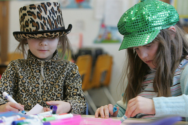 Ayer Elementary School first grade students Isabella Scott, left, and Mary Goodwin, color together during indoor recess on Friday. On January 28, student donated a dollar to American Red Cross for Haiti relief and were allowed to wear a crazy hat to school. Photo by Deborah Parker/January 28, 2009