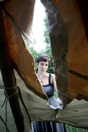 Sarah Johnson is an artist who has built a teepee in her friend's backyard as an art project, closes up part of the tarp in preperation for Saturday when she plans to begin living in the teepee. PHoto by Deborah Parker/July 30, 2009