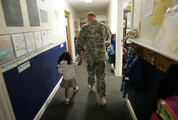 Soldier Brandon Russell holds the hand of  his daugther Hope, 3, after surprising her at school upon returning from a 15 month tour of duty in Iraq Thursday afternoon. photo by deborah parker/october 28, 2010
