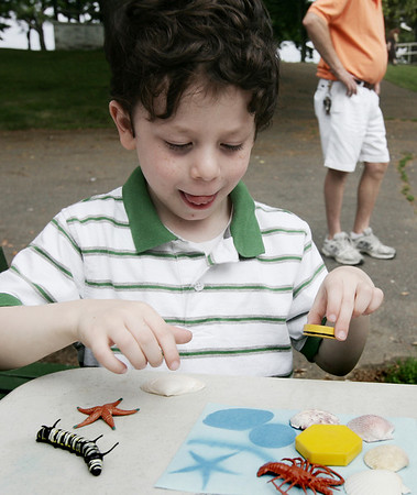 Ryan  Morgenstern, 5, of Salem carefully removes the items from a sun print he created while at the Annual Read Science and Family Picnic at Salem Willows Saturday. The event, open to all Salem Elementary school students and their families, featured science tables along with access to food and rides at the Willows. Photo by Deborah Parker/June 20, 2009