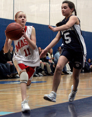 Wenham: Masconomet seventh grader Bell Ives is defended by Lynnfield's Erica Mervillo in front of the net while competeing in the North Shore girls travel basketball Championships held at Gordon College Saturday morning. Photo by Deborah Parker/Salem News Saturday, March 21, 2009.
