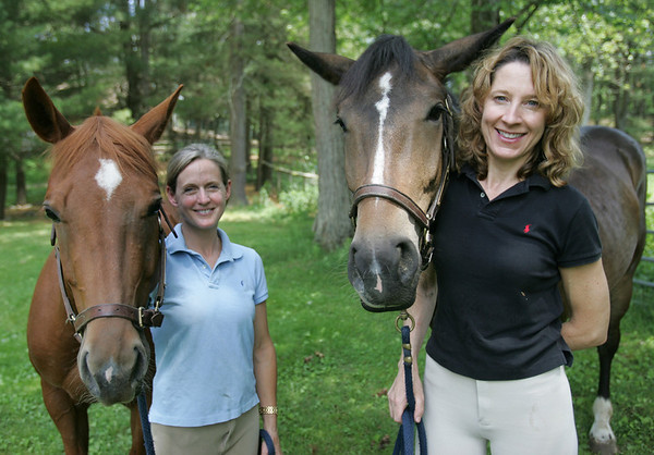 Missy White, left, and Janine Jacques stand with Georgia and Teddy, two horses that they rescued from killpens and are now part of the non profit Hope 4 Horses. Photo by Deborah Parker/June 1, 2010