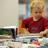 Chase Cann, 2, of Hamilton, checks out the selection of books at the Hamilton-Wenham Public Library book sale for kids Wednesday morning. Photo by Deborah Parker/June 23, 2010