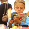 Libby Collins, 6, of Hamilton flips through a book while at the Hamilton-Wenham Public Library book sale for kids Wednesday morning. Photo by Deborah Parker/June 23, 2010