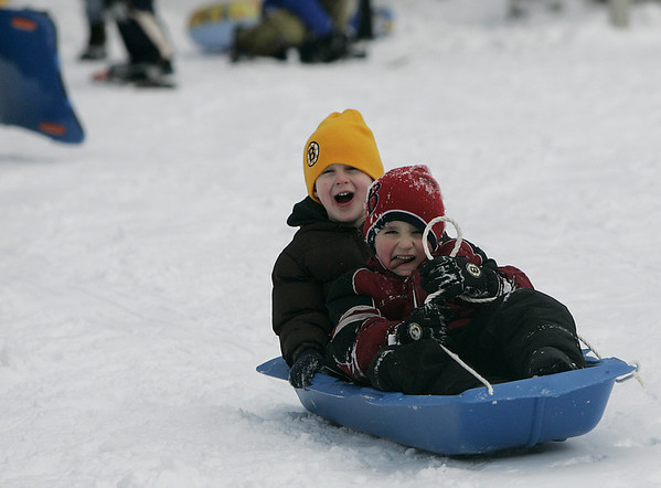 Danvers:Jeffrey Lopes 6, of Danvers sticks out his tongue as he tries to stear the sled while Kevin Wood, 8, also of Davners screams in delight as the two sledded at Endicott Park yesterday afternoon. The park was busy with kids and families sledding as well as other cross country skiing around the property. <br /> Photo by Deborah Parker/Salem News Sunday, January 11, 2009