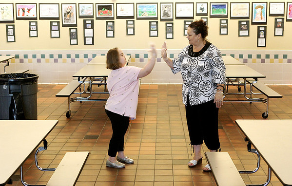 Peabody: Jillian Spinale, 10, a fourth grader at Brown Elementary School had the priveledge of being Principal for Day on Wednesday. Under the supervision of Principal Elaine Metropolis, some over Jillian's responsibilities included teacher evaluations, checking in on classrooms and lunchroom duty. Here, Spinale and Metropolis high five in the lunchroom before the start of the lunch rush.  Photo by Deborah Parker/May 27, 2009