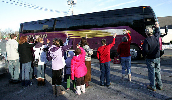 Family and friends wave goodbye as two buses carrying the Massachusetts National Guard 101st Field Artillery Unit leave from their base in Danvers to deploy to Afghanistan. Photo by Deborah Parker/January 6, 2009
