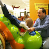Chris Mattina of Marblehead holds the hands of his daughter, Hope, 4, as she plays in the new Children's Area in front the Macy's Men's and Furniture wing at the North Shore Mall Saturday during the new play area's grand opening.  Photo by Deborah Parker/November 14, 2009