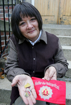 Margo W. R. Steiner, assistant director of marketing at Salem State College holds three pieces of the Berlin Wall. Steiner who was living in Germany in 1989, drove to Berlin to get some pieces of the wall. Photo by Deborah Parker/November 6, 2009