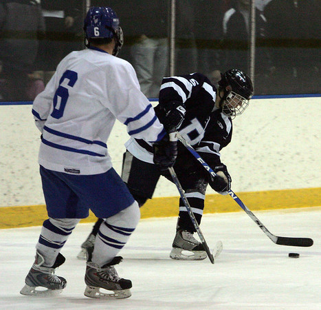 Peabody's Eric Muise is defended by Danvers' DJ Yost in front of the goal during last night's game held at Salem State College. Photo by Deborah Parker/February 1, 2010