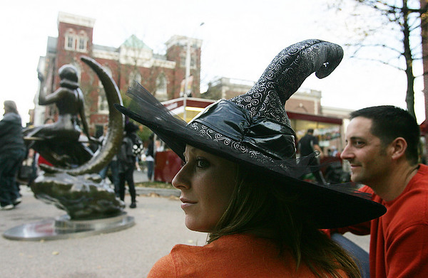 Dressed in a witches hat, Jackie Meluzio of Pennsylvania watches the crowd with Anthony Clanton also of Pennsylvania while near the Bewitched statue Halloween night. Photo by Deborah Parker/October 31, 2009