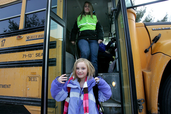 Shannon Underwood, a student at Danvers High School, helps Smith Elementary school student, Haley LeChance cross the street at her bus stop after school. Underwood is a new monitor for the school bus and will ride the bus with students as part of a program aimed at reducing bullying. Photo by Deborah Parker/January 13, 2009