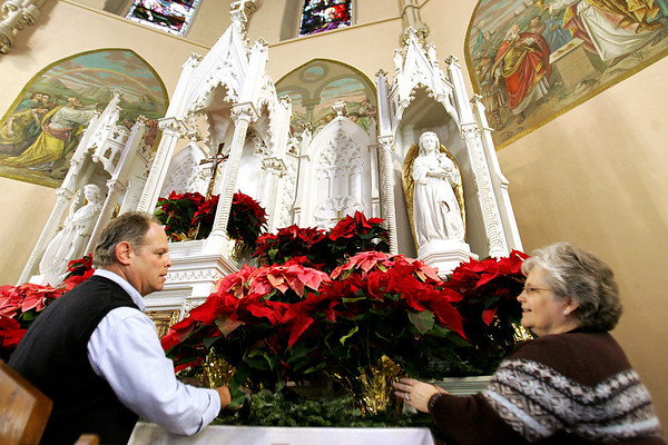 Andrea Schwartz, a parishioner at St. James Parish in Salem, and her husband Laurie,  decorate the altar in preperation for Christmas. Photo by Deborah Parker/December 23, 2009