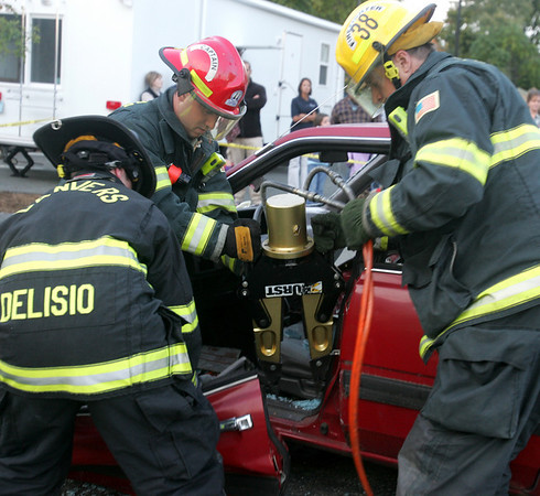 From left, Fire fighter Anthony Delisio, Leuitenant Mike Delisio and Fire fighter Paul Lapointe use the jaws of life in a vehicle extrication demonstration in front of the fire station Thursday evening. The demonstration was part of the department's open house. Photo by Deborah Parker/October 8, 2009