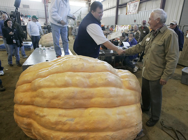 Topsfield: Wes Dwelly of Oakham is congratulated by John Doucet after winning the Topsfield Fair Pumpkin Weigh Off with a weight of 1,464 pounds. Photo by Deborah Parker/Salem News Saturday, October 04, 2008