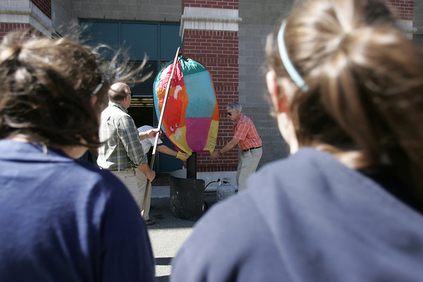 Technology Education teacher Bob Brown, left, along with Stephen Choate and Roger Perham, work to fill a paper balloon with propane outside the Collins Middle School in Salem yesterday afternoon. A group of seventh graders gathered outside the school to watch and see how far their inflated paper balloons would travel. photo by deborah parker/september 21, 2010