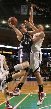 St. John's Pat Connaughton is defended in front of the hoop by Central Catholic's Carson Desrosiers during last night's Division 1 Sectional Finals at the Garden Friday evening. Photo by Deborah Parker/March 5, 2010