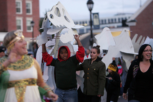 Reimond Reyes, center, a fifth grader at the Carlton School, holds up a paper skeleton of a dinosour during last night's Halloween Parade in down town Salem. Photo by Deborah Parker/October 1, 2009