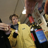 Marblehead: Joanie Pond visiting from Virginia listens as Matt Butterfield of United Liquors talks about the various wines HaleyÕs Wine & Spirits had to sample as part of the Christmas Walk in Marblehead Saturday.  Photo by Deborah Parker/Salem News Saturday, December 13, 2008