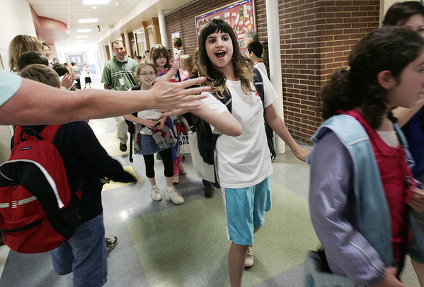 Hannah Elementary School graduating fifth grader, Kiana Bolonesse high fives fourth grade teacher Jamie Reese as the fifth grade class makes their way through the hallways on the last day of school Wednesday afternoon. Photo by Deborah Parker/June 24, 2009