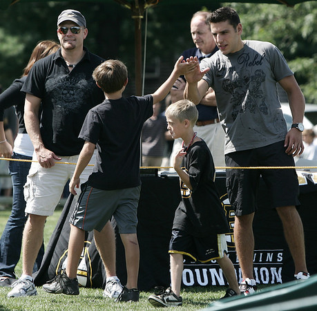 """Boston Bruins players Tim Thomas and Milan Lucic gets high five some fans while judging the Boston Bruins Foundation's """"Swing Like Happy Gilmore Long Drive Contest"""" held at Golf Country in Middleton Tuesday.  Photo by Deborah Parker/September 1, 2009"""