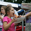 "Teagan Santo, 4, of Salem, gets some helpd holding up her slice of pizza from mom, Jenn, as her sister, Madison, 8, also munches on a slice, during the Heritage Days Pizza Competition held at the Salem Common Monday evening. ""We do this every year,"" said Jenn. ""We're professionals at it by now, we come prepared."" Photo by Deborah Parker/August 9, 2010"