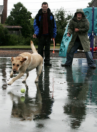 Mike Fuller of Peabody, left, and Ben Olson of Salem didn't let heavy rain keep them from playing catch with Ben's dog, Max at a playground on Salem Neck Saturday morning. Photo by Deborah Parker/August 29, 2009