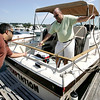 Valter Barcamonte of Peabody, left, helps Brad Schulte, also of Peabody, get ready to leave the dock while at Pope's Landing Marine in Danvers yesterday afternoon. Photo by Debrah Parker/September 4, 2009