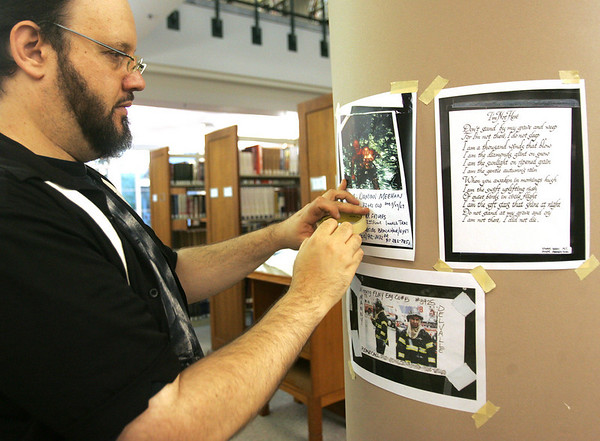 """Artist Dave Gordon sets up part of his exhibition, """"And Then There Was Quiet: New York After the Attack,"""" at the Beverly Public Library Tuesday evening. The show features photographs of the aftermath of the Sept. 11, 2001, attack on New York City. It will run at the libary from Sept. 1-30. Photo by Deborah Parker/August 31, 2010"""