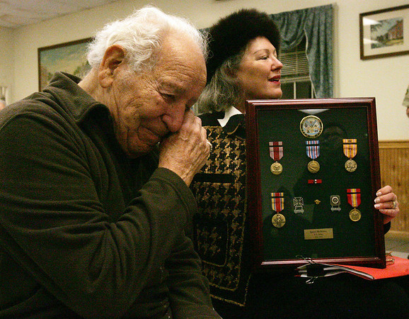 Ipswich resident and World War II veteran, James Medeiros, reacts after accepting several ribbons and medals that he earned during his tour of duty but never received as part of a ceremony in his honor at the VFW Post in Ipswich Friday evening. Major William Duke presented the medals to Medeiros. Next to Medeiros is his wife, Sara. Photo by Deborah Parker/December 4, 2009