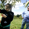Rick Freni of Revere watches as his daughter, Olivia, 7, carefully places an apple in her bag while apple picking with the family at Brooksby Farm in Peabody Friday afternoon. Photo by Deborah Parker/September 25, 2009