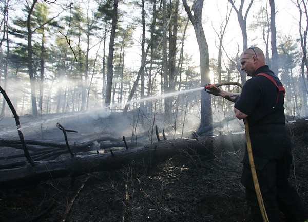 Fire fighter Frank Backry works to extinguish a brush fire in a wooded area behind Danvers High School. Photo by Deborah Parker/April 14, 2010