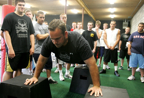"Athletic trainer Patrick Downey shows the Bishop Fenwick team how to do a box push up drill as part of his ""gridiron training"". Downey has started his own business working with many local high school players and teams. He is focusing on hardcore performance with individuals and specific teams. He previously served as a pro football strength and conditioning coach. Photo by Deborah Parker/September 30, 2009"