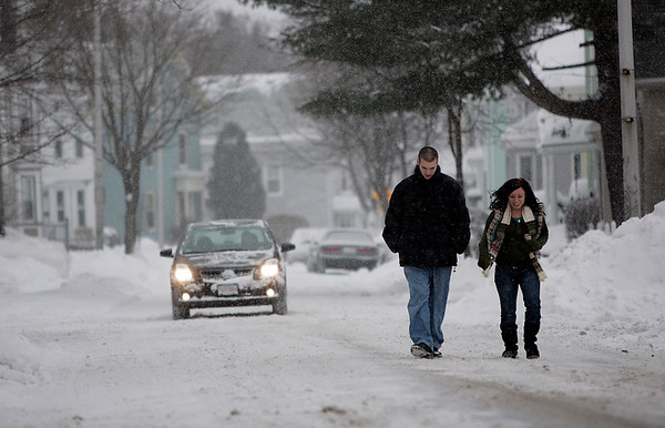 Beverly: Christy Colyer of Hamilton and Rich Tubbs of Beverly walk down a side street off of Cabot Street as snow continued to fall Saturday afternoon. Photo by Deborah Parker/Salem News Saturday, December 20, 2008.