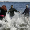 Salem: From left, Elizabeth Black of Beverly, Becky Christie of Salem and Maureen Oslon of Malden quickly make their way into the water during yesterday's Polar Swim at Juniper Point Beach. This is the ninth year that a group of people have gathered to jump into the frigid water. Photo by Deborah Parker/Salem News Thursday, January 01, 2009