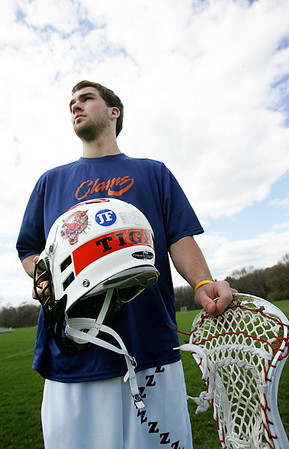"Eli Hayward, center, a senior and captian of the Ipswich lacrosse team, organized an effort to put the intials ""JF"" on the team helmets this year in honor of classmate Jason Foster. Foster was killedin a car accidnet over the summer. Hayward did not know Foster well, but the lacrosse player felt the need to pay tribute to his classmate. Photo by deborah Parker/APril 12, 2010"
